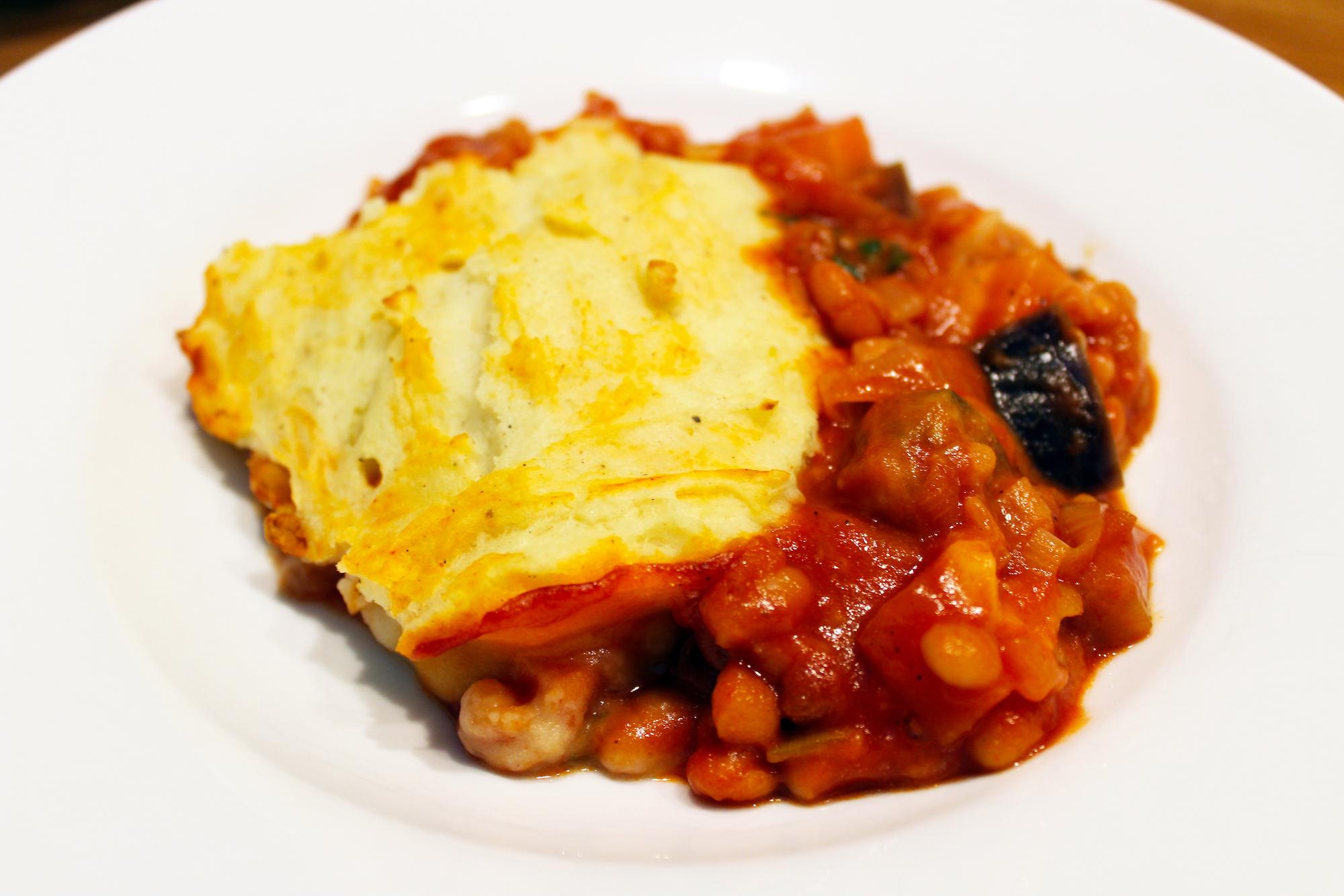 Vegetarische ovenschotel met aubergine, bonen in tomatensaus en puree